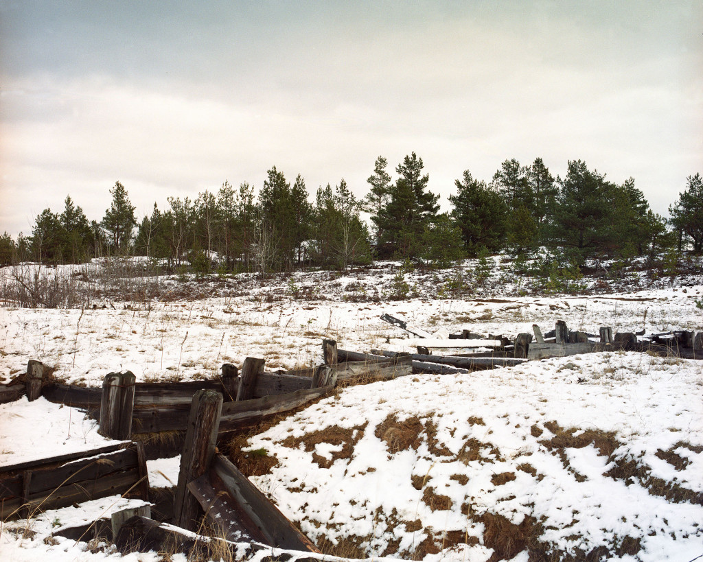 Simon Menner: From the series Camouflage, 2010. Right of the center of the image, there is a wooden plank behind the trench, which is slightly pointing upwards. Sniper to the right of this plank under a white tarp, the muzzle is visible.