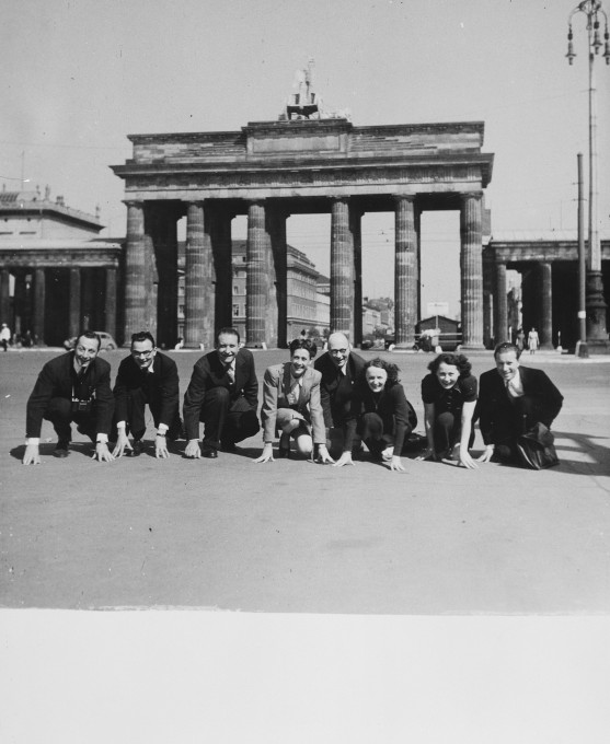 A company of French singers and dancers poses in front of the Brandenburg Gate while on a performance tour in Germany. Sadie Rigal, who is actually a Jew in hiding, is pictured in the centre. Date: 1943. (On the far left is her dance partner, Frederic Apcar. Edith Piaf is show third from the right.) Photo Credit: United States Holocaust Memorial Museum, courtesy of Sadie Rigal Waren.