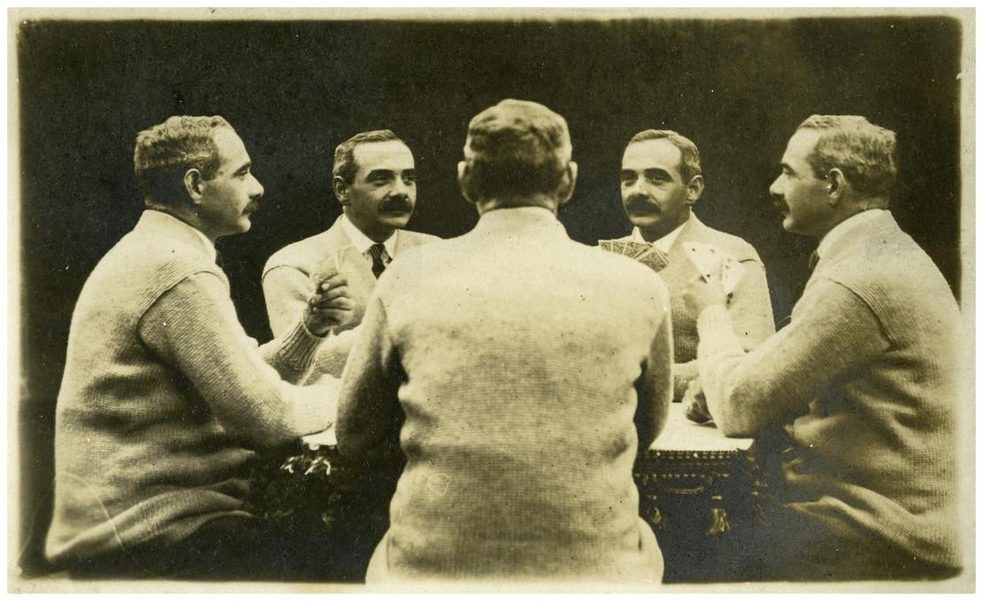 Slika 5. Zelo priljubljen motiv je bil, da so portretiranca posedli za mizo, kjer se je zdelo, kot da igra karte s še štirimi kloni samega sebe. V takšnem petkratnem portretu intenzivnost igralčevega obličja ustvari notranjo dramo. Fotografska razglednica iz zasebne zbirke umetnikov.