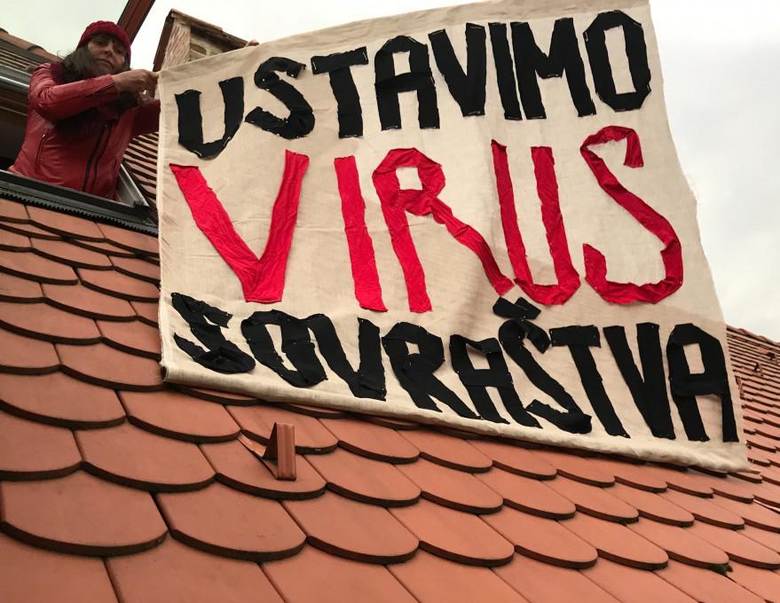 Slika 1. Irena Woelle, Ustavimo virus sovraštva, protest z zastavo, 21. marec 2020, Ljubljana. Fotografija: Vuk Ćosić.